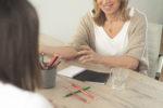 Alice Nilsson führt eine Beratung durch. Am Tisch lieben Buntstifte und Notizblöcke.